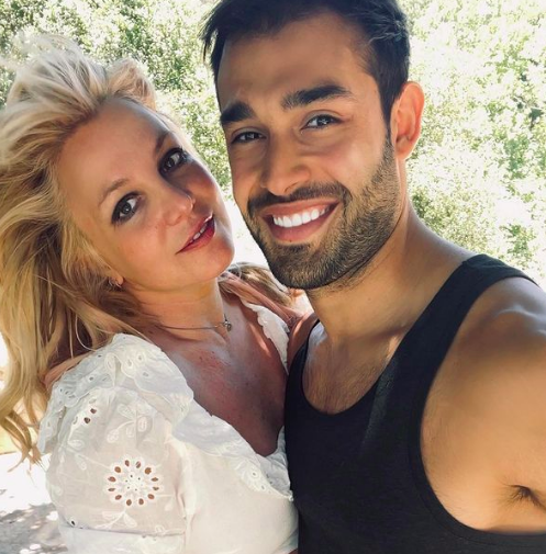 Britney Spears and Sam Asghari smile in a photo taken in a garden.