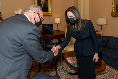 Angelina Jolie shakes hands with Sen. Chuck Schumer. She wears a black suit and black face mask.