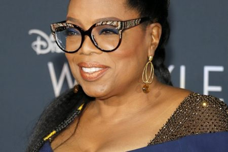 Oprah Winfrey smiles at a red carpet premiere. Her hair is tied back and she wears fancy glasses and a navy dress.