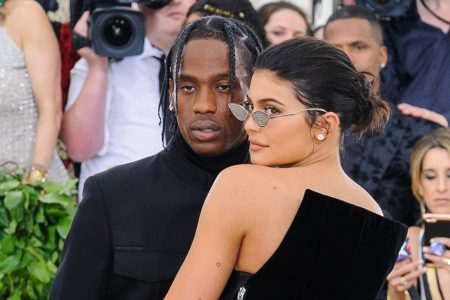 Travis Scott and Kylie Jenner pose at a red carpet event, both wearing black.