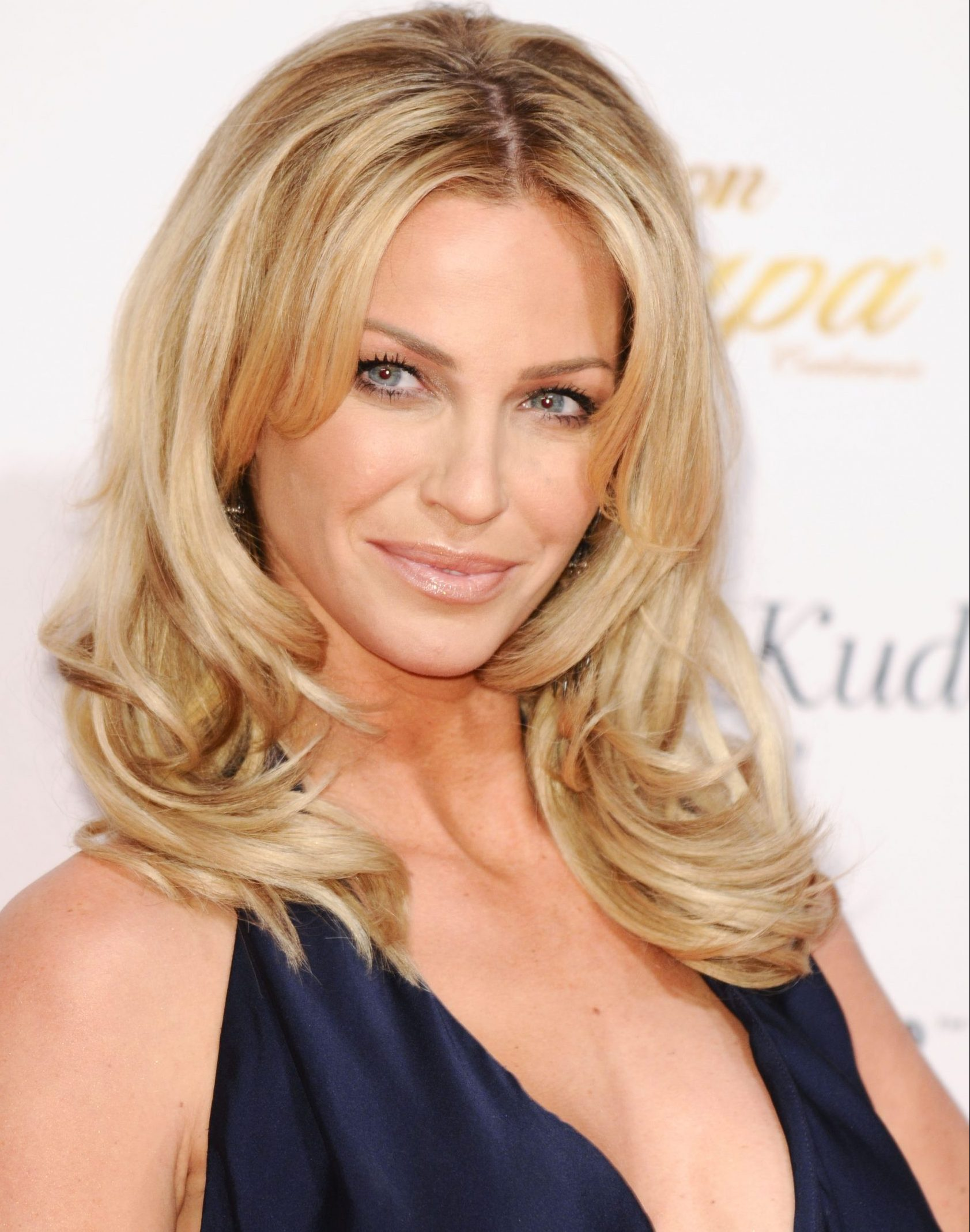 Sarah Harding smiles at a red carpet event. She has layered blonde hair and wears a black dress.
