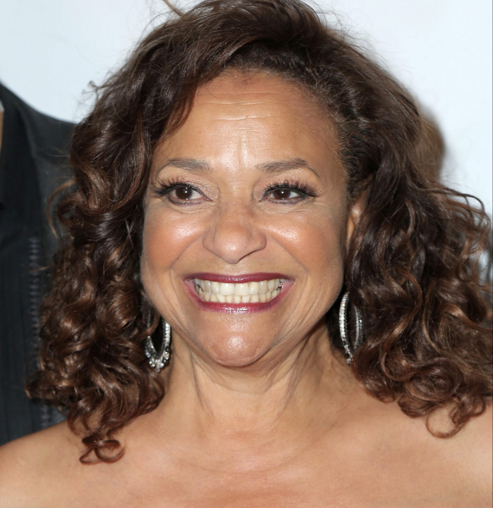 Debbie Allen smiles at a red carpet event. She is a beautiful Black woman with curly brown hair that sits on her shoulders.
