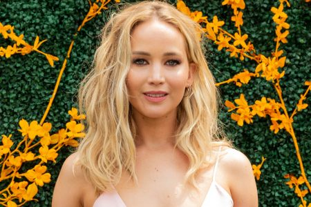 Jennifer Lawrence smiles against a backdrop of greenery and yellow flowers.