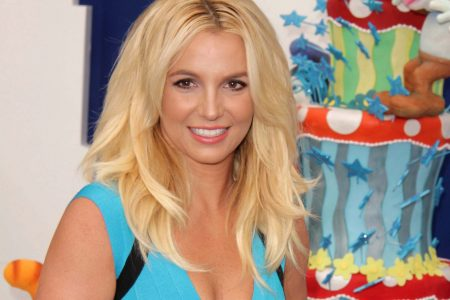 Britney Spears wears a blue dress and smiles at a press event.