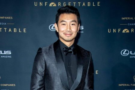 Simu Liu dressed in a shiny charcoal suit, smiling at a red carpet event.