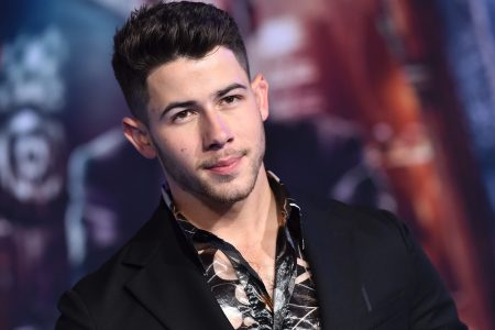 Nick Jonas from the chest up at a red carpet event. He wears a black suit jacket and a dark patterned shirt with the top button undone.