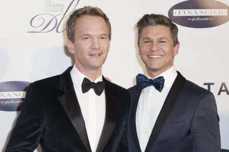 Neil Patrick Harris & David Burtka wear tuxedos and smile together at a red carpet event.