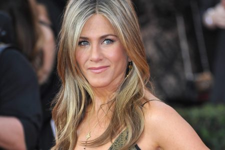 Jennifer Aniston poses at a red carpet event. She has wavy golden hair and wears a dark gold dress.