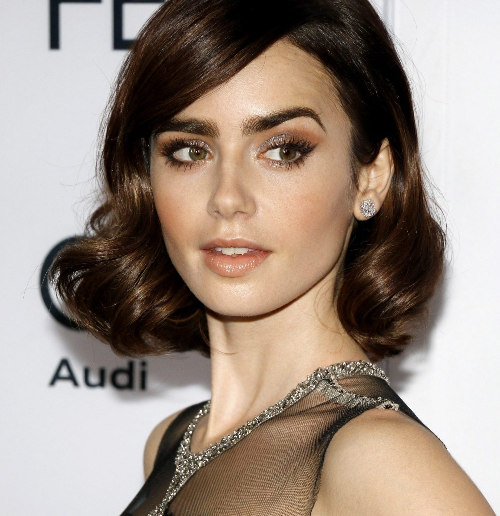 Lily Collins smiles at a red carpet event.