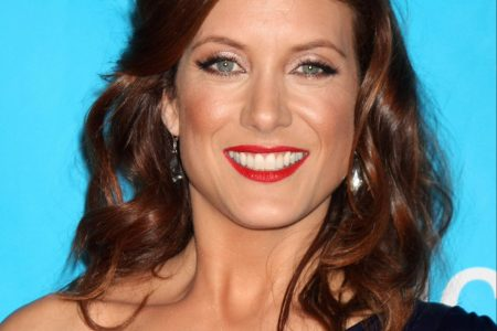 Kate Walsh smiles at a red carpet event. She has red hair and wears a one shoulder, purple dress.